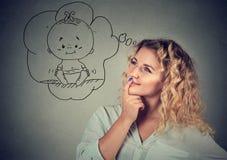 Junge Frau, die vom Baby träumt lizenzfreies stockbild