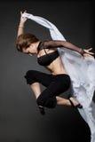 Junge Frau, die von einem sich entwickelnden Gewebe springt. Stockfotografie