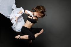 Junge Frau, die von einem sich entwickelnden Gewebe springt. Stockbild