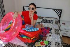 Junge Frau, die von einem Weltreisesitzen träumt Mädchenverpackungskoffer auf Boden zu Hause stockfotos