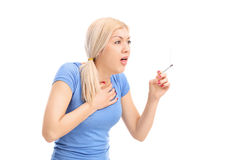 Junge Frau, die von einer Zigarette hustet Stockbild