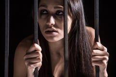 Junge Frau, die von hinter Gittern schaut Stockfotografie