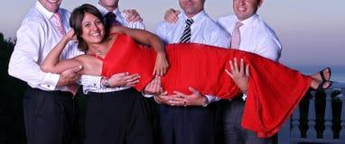Junge Frau, die von vier Männern an einer Party angehoben wird Stockbild