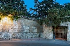 Junge Frau, die vor dem Eisentor ein Stein und eine Backsteinmauer errichtet im 16. Jahrhundert in Alcala de Henares geht Lizenzfreie Stockbilder