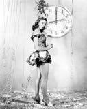 Junge Frau, die vor einer Uhr, Sylvesterabende feiernd steht (alle dargestellten Personen sind nicht längeres lebendes und kein Z Stockbilder