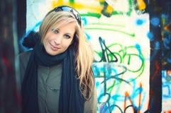 Junge Frau, die vor Graffitiwand steht stockbilder