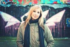 Junge Frau, die vor Graffitiwand steht stockbild