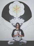 Junge Frau, die vor großer Mandalamalerei auf der Wand meditiert Stockbilder