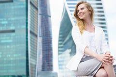 Junge Frau, die vor Stadtgebäuden sitzt Lizenzfreie Stockfotos
