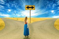 Junge Frau, die vor zwei Straßen steht Lizenzfreie Stockfotos