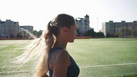 Junge Frau, die während des sonnigen Morgens auf Stadion läuft stock video