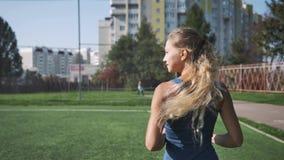 Junge Frau, die während des sonnigen Morgens auf Stadionsbahn läuft stock video footage