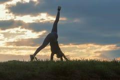 Junge Frau, die Wagenrad auf dem sch?nen Sonnenaufgang Gras Morgengymnastik tut lizenzfreies stockbild