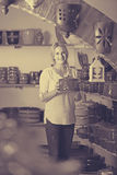 Junge Frau, die Waren des keramischen Tellers im Atelier vorwählt Lizenzfreie Stockfotografie