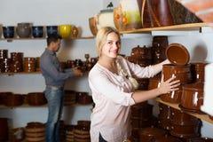 Junge Frau, die Waren des keramischen Tellers im Atelier vorwählt stockfotografie