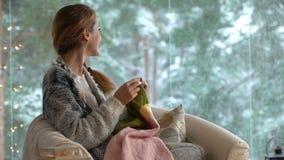 Junge Frau, die warme Wollstrickjacke im Wohnzimmer gegen Schneelandschaft von der Außenseite strickt stock footage