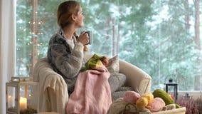 Junge Frau, die warme Wollstrickjacke im Wohnzimmer gegen Schneelandschaft von der Außenseite strickt stock video footage
