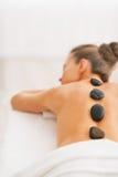 Junge Frau, die Warmsteinmassage empfängt. hintere Ansicht Stockbild