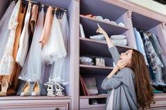 Junge Frau, die was wählt, in einem Wandschrank zu tragen lizenzfreie stockbilder