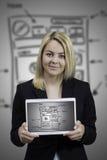 Junge Frau, die Websitedrahtrahmenskizze auf Tablette zeigt Stockbild