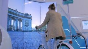 Junge Frau, die wechselwirkende Fahrradsimulatormaschine verwendet