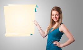 Junge Frau, die weißen origami Papierexemplarplatz anhält Lizenzfreie Stockfotos