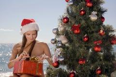 Junge Frau, die Weihnachten im Strandurlaubsort feiert Stockbild