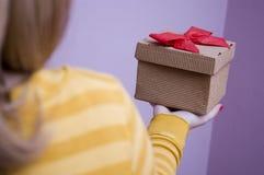 Junge Frau, die Weihnachtsgeschenke anhält Stockfoto