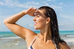 Junge Frau, die weit weg im Strand schaut stockfotografie