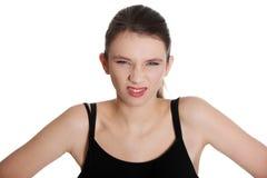 Junge Frau, die Wekzeugspritze knittert und Augen schielt. Stockbilder