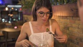 Junge Frau, die wenn Restaurant dinning ist, geglättet wird Schönheit, die Salat am romantischen Abendessen im eleganten Restaura stock video