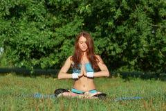Junge Frau, die Yogaübung auf Park tut Stockbild