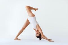 Junge Frau, die Yoga asana abwärtsgerichteten Hund tut Stockfotografie