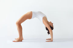 Junge Frau, die Yoga asana aufwärts Bogen-Rad-Haltung tut Stockfotos