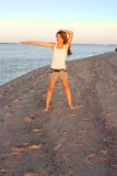 Junge Frau, die Yoga auf Strand tut Stockbild