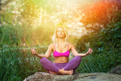 Junge Frau, die Yoga in der schönen Natur des Morgens nahe Fluss tut Stockfotografie