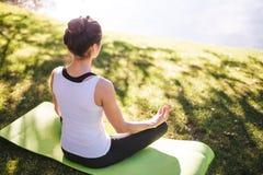 Junge Frau, die Yoga im Morgenpark nahe See tut Stockfotografie