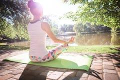 Junge Frau, die Yoga im Morgenpark nahe See tut Lizenzfreies Stockbild