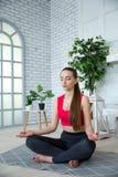 Junge Frau, die Yoga im Morgenpark tut Stockfoto