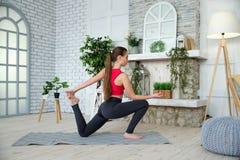 Junge Frau, die Yoga im Morgenpark tut Stockbild