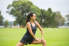Junge Frau, die Yoga im Park ausübt Stockbild