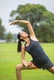 Junge Frau, die Yoga im Park ausübt Lizenzfreie Stockfotografie