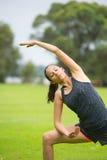 Junge Frau, die Yoga im Park ausübt Stockbilder