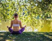 Junge Frau, die Yoga im Park nahe See tut Lizenzfreies Stockbild