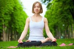 Junge Frau, die Yoga im Park tut Lizenzfreies Stockbild