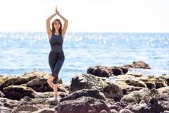 Junge Frau, die Yoga im Strand tut Stockfotos