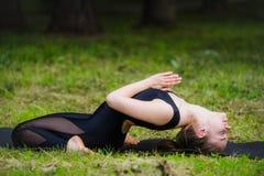 Junge Frau, die Yoga, stützende spinale Torsionsposition tut Stockbild