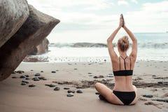 Junge Frau, die Yoga am Strand tut Stockbilder