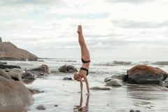 Junge Frau, die Yoga am Strand tut Stockfoto