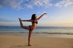 Junge Frau, die Yoga am Strand tut Stockfotografie